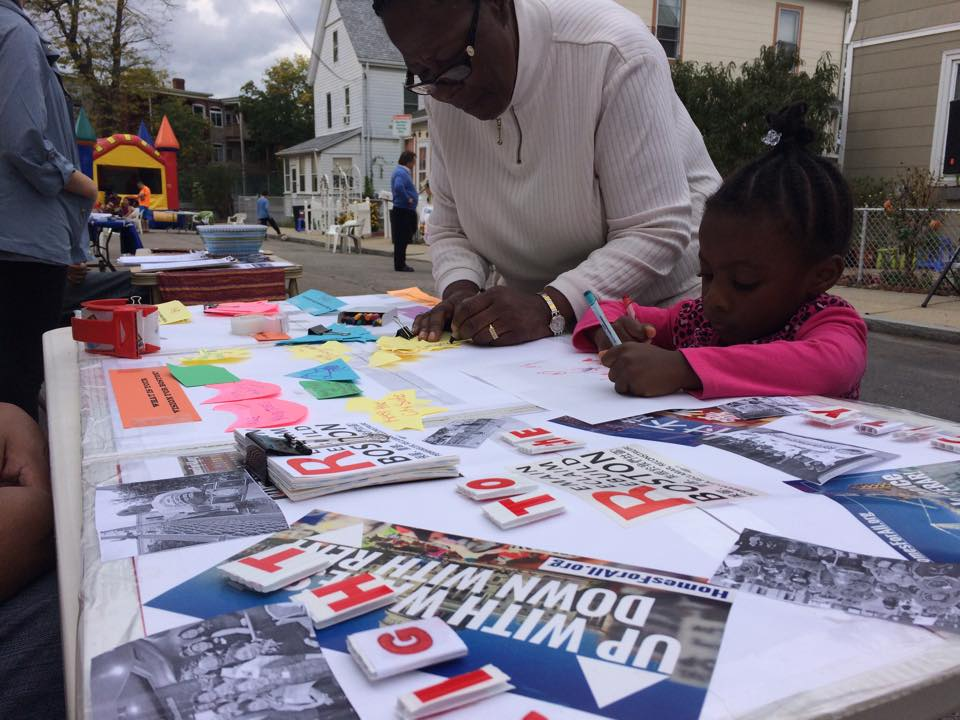 A Black woman and child making signs up a table with posters and literature