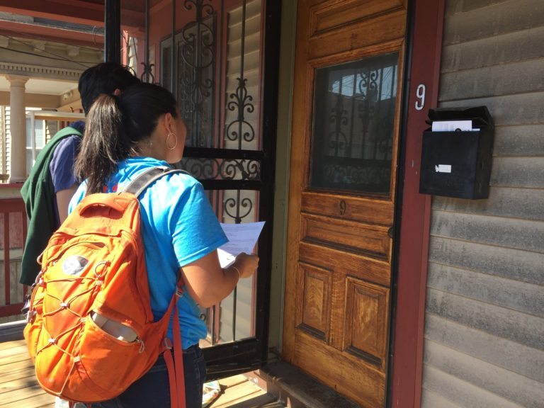 A young person in a blue shirt and orange backpack knocking on a door